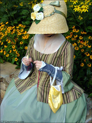 Using a knotting shuttle while wearing 18th century clothing.
